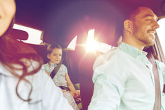 Happy family with little child driving in car. Family, transport, safety, road trip and people concept - happy men and women with little child driving in car Stock Photography