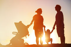 Happy family with little child and stroller play at sunset Stock Image