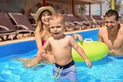 Happy family with little child in swimming pool. Outdoors stock photos