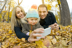 Happy family. With little child take Selfie on telephone, outing in autumn park Stock Photo
