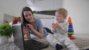 Happy family, little cute child boy with young mum clap hands while watching cartoons on laptop computer lying on floor. At room stock footage