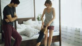Happy family and little cute daughter dancing and turning around near bed in bedroom at home