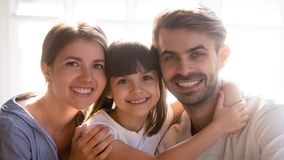 Happy family with little cute daughter smiling looking at camera stock photography