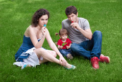 Happy family with little daughter sitting on green. Grass stock photography