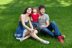 Happy family with little daughter sitting on green Stock Images