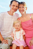 Happy family with little girl on beach Stock Photos
