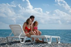Happy family with little girl on beach. Happy family with little girl in chaise lounge on beach Stock Photos