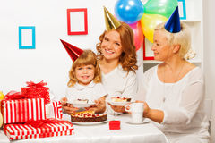 Happy family at little girl birthday party. Happy smiling family by the table on children girls birthday eating birthday cake with many present near Stock Images