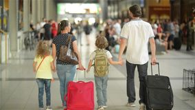 Happy family with little girl and boy going on railway station, mother father and the kids walk through the airport with