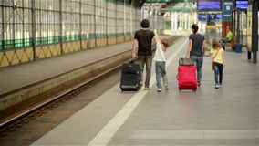 Happy family with little girl and boy going on railway station, mother father and the kids walk through the airport with. Suitcases, journey stock video