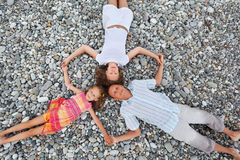 Happy family with little girl lying on beach stock photo