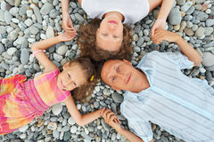 Happy family with little girl lying on stony beach Stock Image