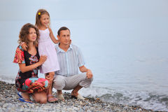 Happy family with little girl on stony beach Stock Photo