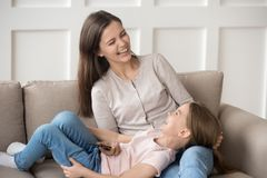 Happy family little kid daughter and mom laughing holding phone stock images