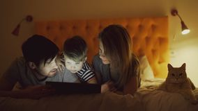 Happy family with little son and funny cat lying in bed at home and using tablet computer for watching cartoon movie. Before sleeping time Royalty Free Stock Image