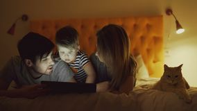 Happy family with little son and funny cat lying in bed at home and using tablet computer for watching cartoon movie. Before sleeping time stock video