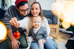 Happy family playing with Christmas balls at home. Happy family and little son playing home on Christmas holidays. New Year`s holidays Royalty Free Stock Image