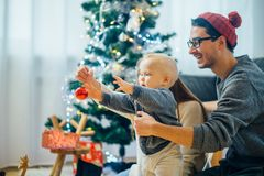Happy family playing with Christmas balls at home. Happy family and little son playing home on Christmas holidays. New Year`s holidays. Toddler with mom and dad Royalty Free Stock Image
