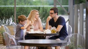 Happy family with son spending time together in outdoor terrace. Wife and husband talking while boy eating dessert with stock footage