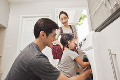 Happy Family loading clothes into washing machine in home stock photo