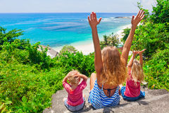 Happy family look at sea surf on white sand beach. Happy family travel - mother, baby son, daughter sit on cliff steps, look at sea surf on white sand beach royalty free stock image