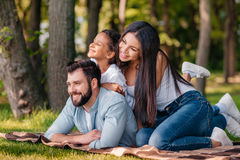Happy family looking away while resting on blanket together Royalty Free Stock Photography