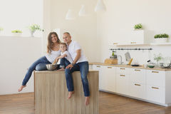 Happy family looking at the camera in kitchen. Happy smiling caucasian family in the kitchen Royalty Free Stock Photo