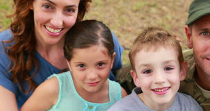 Happy family looking at camera. In park stock video footage