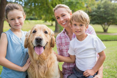 Happy family looking at camera and playing with their dog Royalty Free Stock Photos