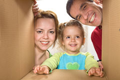 Happy family looking through a cardboard box Stock Images