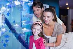 Happy family looking at fish tank Royalty Free Stock Photo