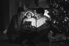 Happy family looking inside of Christmas gift box Stock Photos