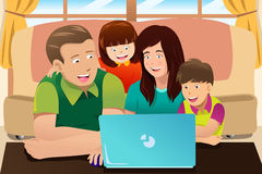 Happy family looking at a laptop Royalty Free Stock Photo