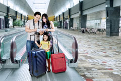 Happy family looking a map on tablet. Asian family doing holiday trip and looking a map on the digital tablet at the airport hall Stock Photography