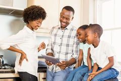 Happy family looking at tablet Stock Images