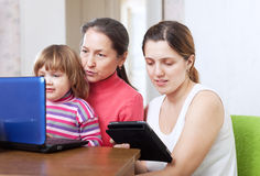 Happy family looks electronic devices Stock Images