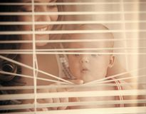 Happy family, love, trust. Woman with child smile at window shutters Stock Image