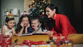 Cheerful big family of four people are reading a book. New year night at the foot of the Christmas tree. Happy family of lovely mother and two little girls and stock video
