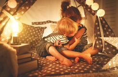 Happy family children brother and sister play, laugh and hug i. Happy family loving children brother and sister play, laugh and hug in dark tent in playroom at royalty free stock image