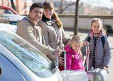 Happy family with luggage near car. Happy family with two daughters  with trollers near car Stock Images
