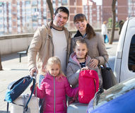 Happy family with luggage near car. Happy young parents  with two daughters  with trollers near car Stock Photography