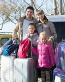 Happy family with luggage near car. Happy young parents  with two little  daughters  with trollers near car Royalty Free Stock Image