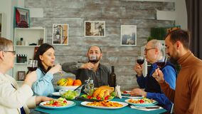 Happy family during lunch toasting with red wine