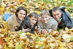 Happy family lying in autumn park Stock Photo