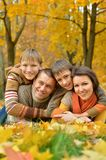 Happy family lying in autumn park Royalty Free Stock Photo