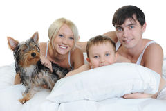 Happy family lying in bed. In the morning. Isolated on white background Stock Photo
