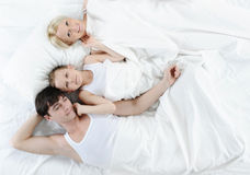 Happy family lying in bed Stock Images