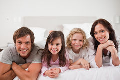 Happy family lying in a bed Stock Image