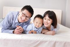 Happy family lying on bed Royalty Free Stock Images