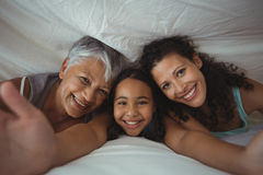 Happy family lying on bed in bed room. Portrait of happy family lying on bed in bed room at home Royalty Free Stock Images